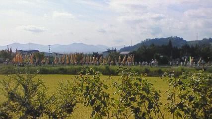 秋の実りの横を行く祭の行列