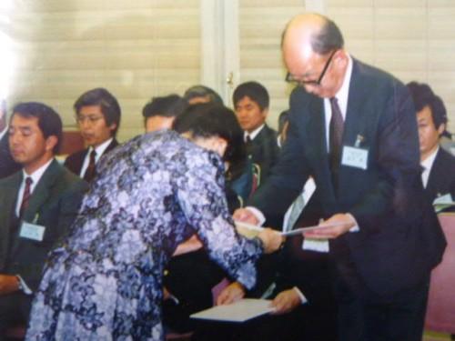 1988年(平成4年)秋山財団初代理事長・秋山喜代から贈呈書を受け取る鈴木章先生