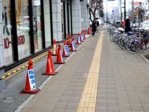 左:「駐輪禁止」の三角コーンが約50メートル、右:自転車が整然と