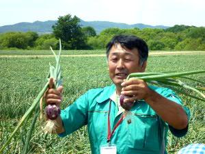 タマネギ畑で生産者・吉田さんの熱く暑いご説明