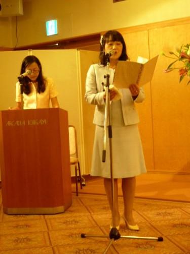 冒頭の詩の朗読と司会者・柴崎由紀さん(左)