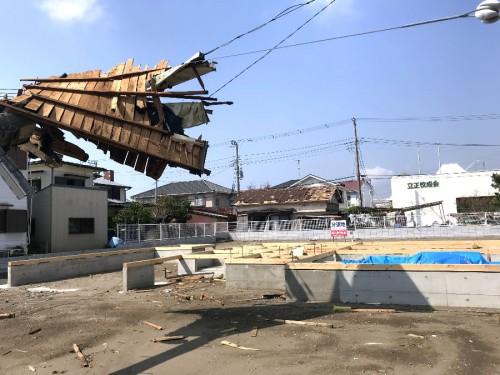 倒壊した電柱の先には瓦が飛んだ屋根の家